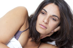 Sad woman lying in bed Stock Photography