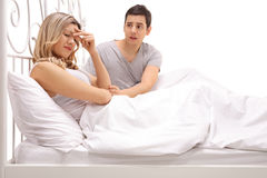 Sad woman lying in bed with a guy comforting her Royalty Free Stock Photography