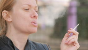 Sad woman without makeup nervously smokes in the street stock footage