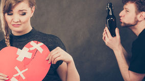 Sad woman and man addicted to alcohol. Broken heart. Unhappy couple. Family and alcoholism problems. Addiction and trouble of drinking. Man with alcohol bottle stock image