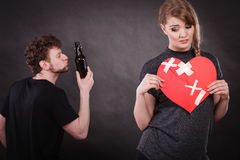 Sad woman and man addicted to alcohol. Broken heart. Royalty Free Stock Images
