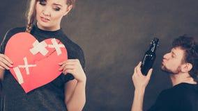 Sad woman and man addicted to alcohol. Broken heart. Royalty Free Stock Photos