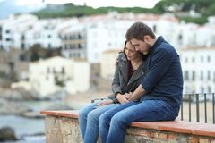 Sad woman and man comforting her on a ledge. Sad women and men comforting her on a ledge with a town in the background stock images
