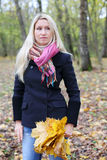 Sad woman with maple leaflets. Sad beautiful woman with yellow maple leaflets and at side in autumn forest. Shallow depth of field royalty free stock images
