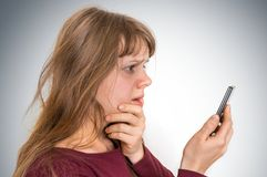 Sad woman with mobile phone - bad news concept royalty free stock images