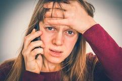Sad woman with mobile phone - bad news concept stock image