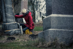 Sad Woman in Mourning Touching a loved one's Gravestone Royalty Free Stock Photo
