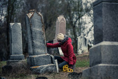 Sad Woman in Mourning Touching a loved one's Gravestone. Lonely Sad Young Woman in Mourning with Sunflowers Touching a loved one's Gravestone in a Cemetery Royalty Free Stock Photography