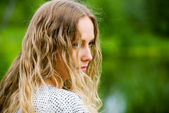 Sad young fashion woman with long curly hairs outdoor Royalty Free Stock Photo