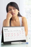 Sad woman with negative pregnancy test. And calendar. A concept being failed to get pregnant stock photos