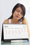 Sad woman with negative pregnancy test. And calendar. A concept being failed to get pregnant stock images