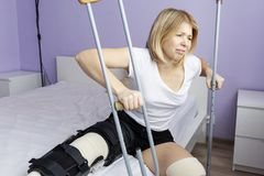 Sad woman after an operation on her leg is sitting on the bed royalty free stock photography