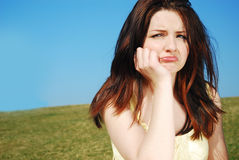 Sad woman outdoors. A sad young brunette woman outdoors in a field with a blue sky royalty free stock images