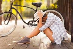 Sad woman park. Sad young woman sitting at the park next to bicycle Stock Photos