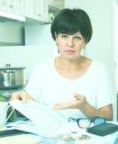 Sad woman paying bills Royalty Free Stock Image