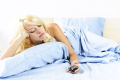 Sad woman with phone in bed Stock Photography