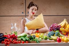 Sad woman with pillow watching at food Stock Image