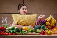 Sad woman with pillow watching at food Royalty Free Stock Images