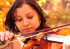 Sad Woman Playing Violin in Autumn. Crying woman playing her violin with an autumn color backdrop with a tear falling from her eye Stock Photography