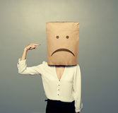 Sad woman pointing at paper bag Royalty Free Stock Images