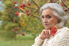 Sad woman posing with berries. Sad senior beautiful   woman posing with berries Stock Images