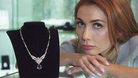 Sad woman posing with an expensive diamond necklace at the store. Close up of a beautiful sad woman looking unhappy and disappointed posing with an expensive royalty free stock images