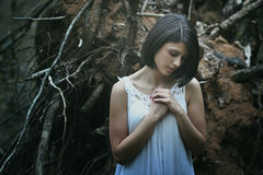 Sad woman praying in dark wood Royalty Free Stock Photography