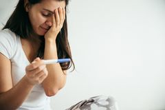 Sad woman with pregnancy test. Sad woman looking on pregnancy test unexpected stock images