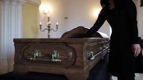 Sad woman putting red rose into coffin at funeral stock video footage
