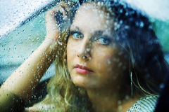 Sad woman in a car in the rain. Sad young woman looking through the car window with a rain drops Royalty Free Stock Photos