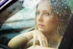 Sad young woman in a car looking out window