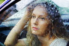 Sad woman looking through car window Stock Photos