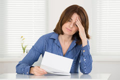 Sad Woman Reading Document Royalty Free Stock Images