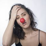 Sad woman with red nose. A studio portrait of a pretty young woman with a very sad expression on face Stock Image