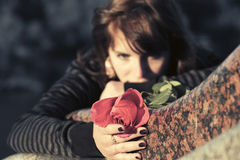Sad woman with a red rose lying on tombstone Stock Image