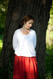 Sad woman in red sarafan. Near a tree Royalty Free Stock Photography