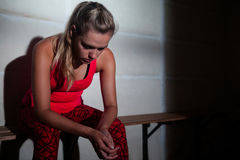 Sad woman relaxing on bench. In fitness studio Stock Photography