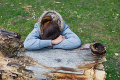 Sad woman resting on tree trunk Royalty Free Stock Image