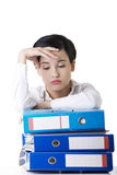 Sad woman with ringbinders sitting at the desk. Stock Photo