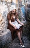 Sad woman in a rustic dress sitting near old brick wall in old house and trying to dress a white shoe. Cinderella style stock image