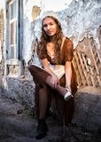 Sad woman in a rustic dress sitting near old brick wall in old house and trying to dress a white shoe. Cinderella style stock images