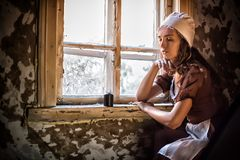 Sad woman in a rustic dress sitting near window in old house feel lonely. Cinderella style Royalty Free Stock Images