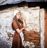 Pensive young woman in a rustic dress standing near old brick wall in old house feel lonely. Cinderella style stock photos