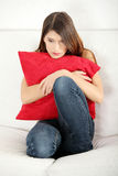 Sad woman's sitting and squeezeing pillow. Stock Photo