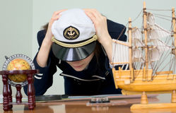 Sad woman in a sea uniform at table royalty free stock photography