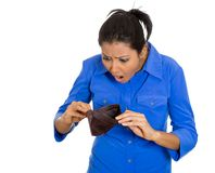 Sad woman showing empty wallet. Closeup portrait of shocked, upset, sad, unhappy young woman standing showing empty brown wallet, isolated against white Royalty Free Stock Photography