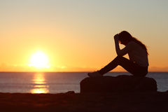 Sad woman silhouette worried on the beach. At sunset with the sun in the background Royalty Free Stock Images