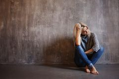 Sad woman sits on the floor. Depression and chronic fatigue. Young beautiful blonde in a gray sweater and jeans royalty free stock photo