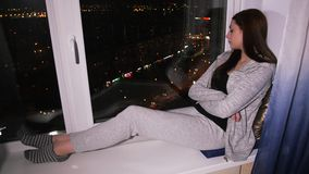 Sad woman sits on window sill, look at night city