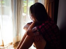 Sad woman sitting alone in a empty room beside window or door. Sad woman hug her knee and cry. Sad woman sitting alone in a empty room beside window or door Royalty Free Stock Photo
